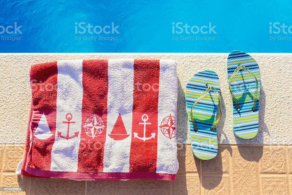 Bathing slippers and bath towel at swimming pool stock photo