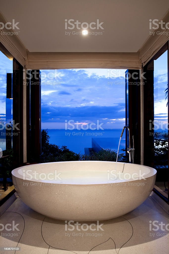 A bathroom and bathtub looking out to the skyline stock photo