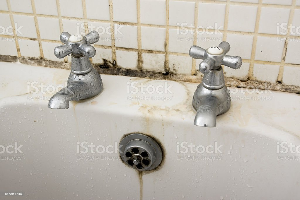 Bathroom dirt and mould on grouting and tiles behind taps royalty-free stock photo