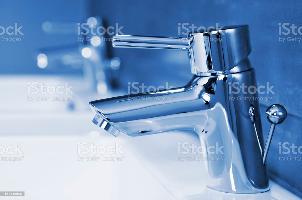 Bathroom interior with close-up of water taps, blue toned royalty-free stock photo