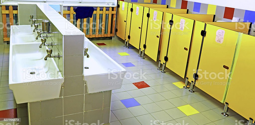 bathroom of a nursery with white sinks and toilet doors stock photo