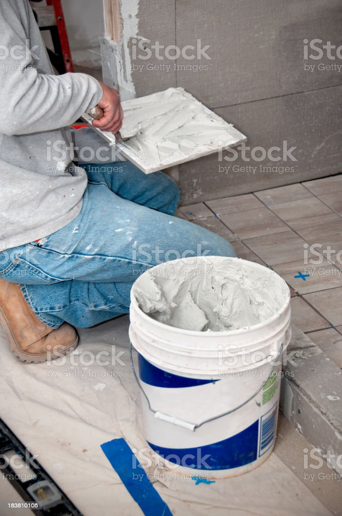 Bathroom Remodeling: Contractor putting mortar on Tiles stock photo