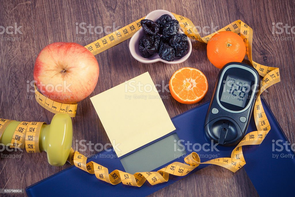 Bathroom scale, glucometer with result of measurement, healthy food, dumbbells stock photo