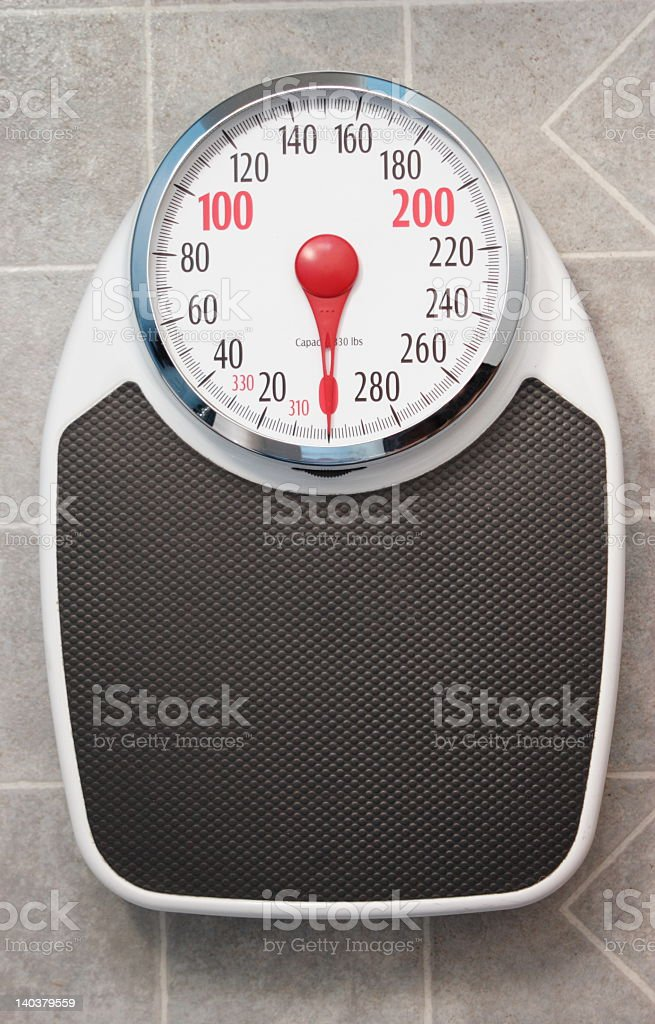 Bathroom scale isolated on grey tiles stock photo