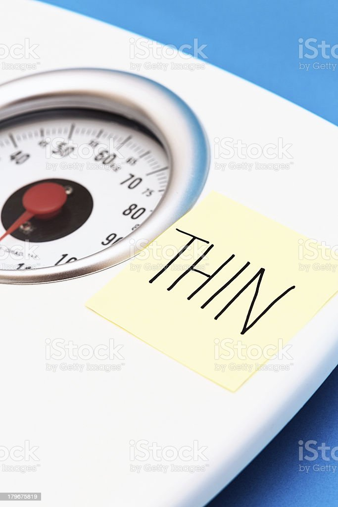 Bathroom scales with label saying THIN: ambition or obsession? royalty-free stock photo