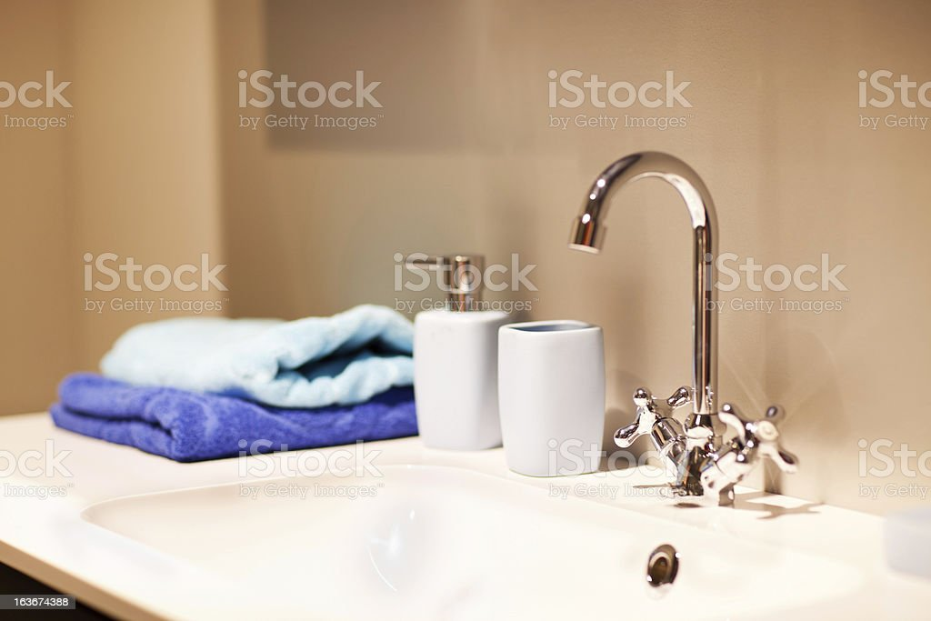 Bathroom sink with chrome faucet and towels stock photo