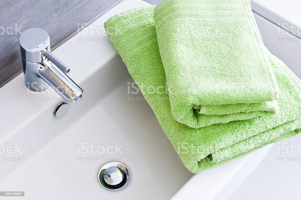 Bathroom sink with two clean green towels in different sizes stock photo