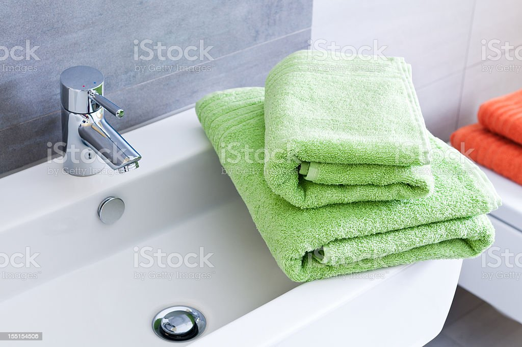 Bathroom sink with two green towels royalty-free stock photo