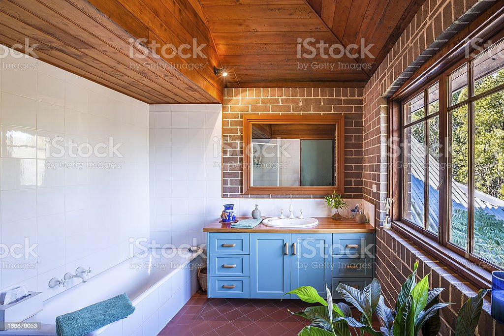 A bathroom with a tiled wall and wooden ceiling stock photo