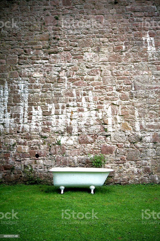 Bathtub on the lawn against a stone wall stock photo