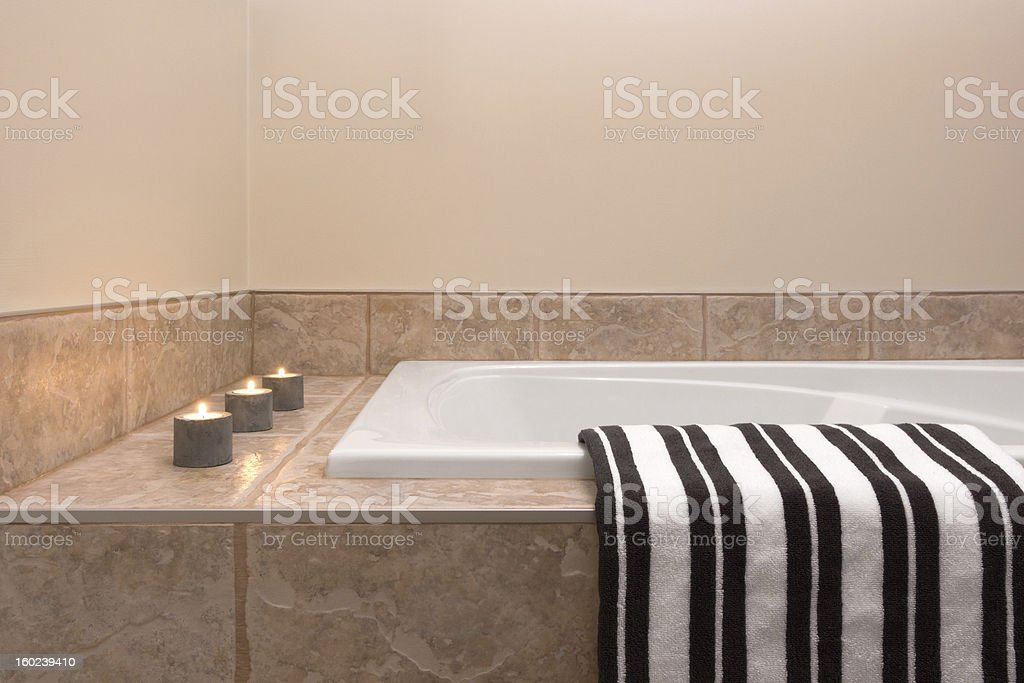 Bathtub, striped towel and candle lights royalty-free stock photo