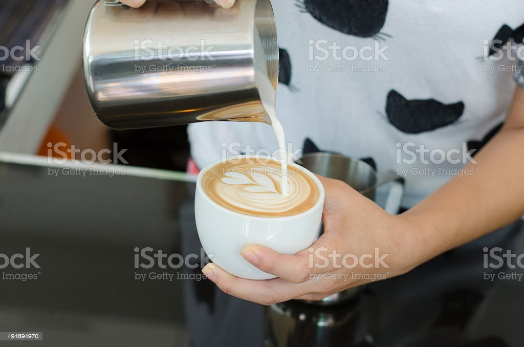 batista making coffee with latte art stock photo