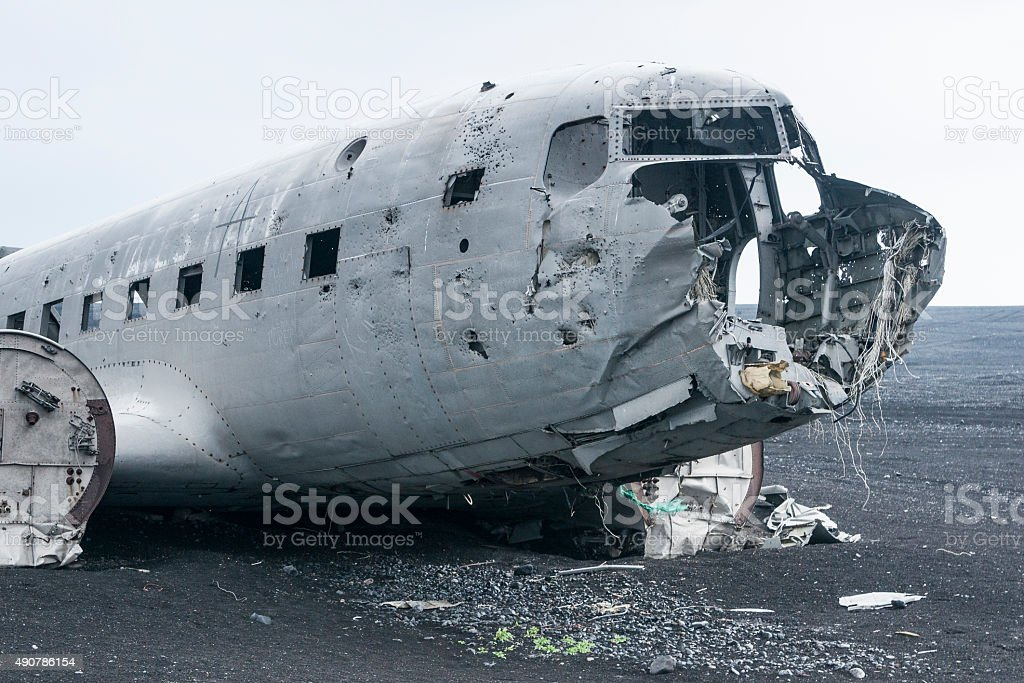 Battered airplane rusting in lava field stock photo