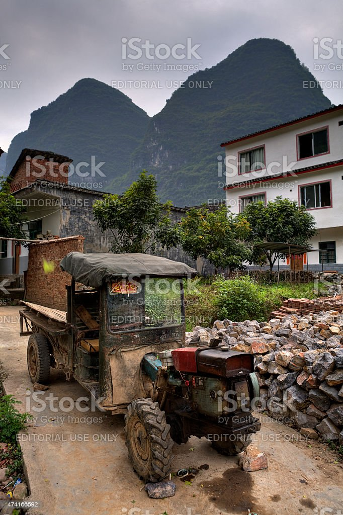 Battered ancient farmer tractor stands in peasant village, Guangsi, China. stock photo