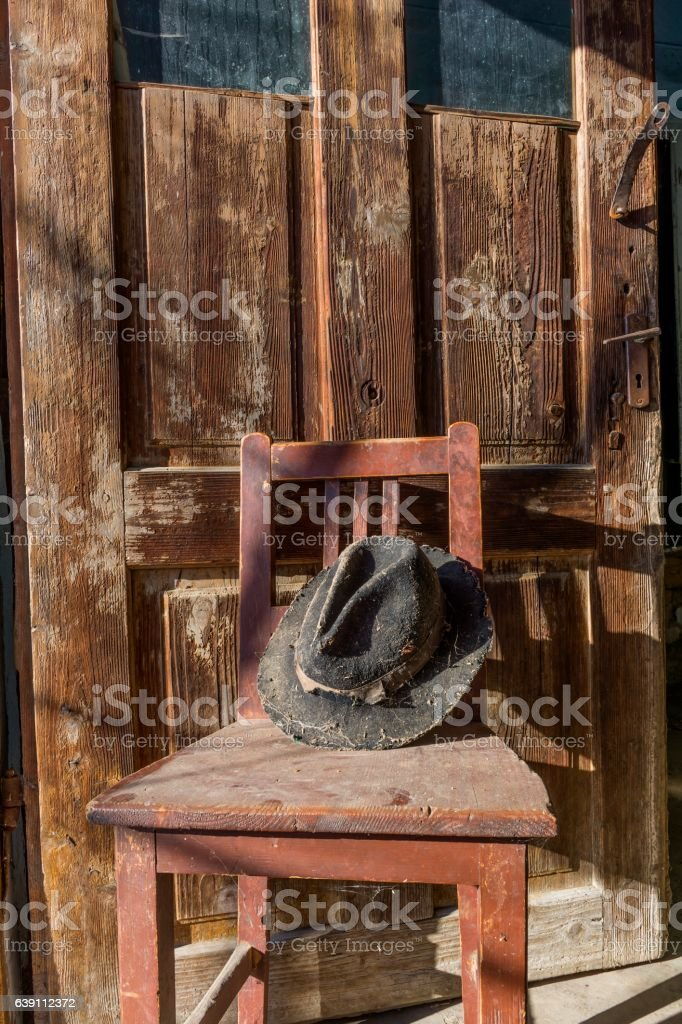 Battered old hat damaged by clothes moth on vintage background. stock photo