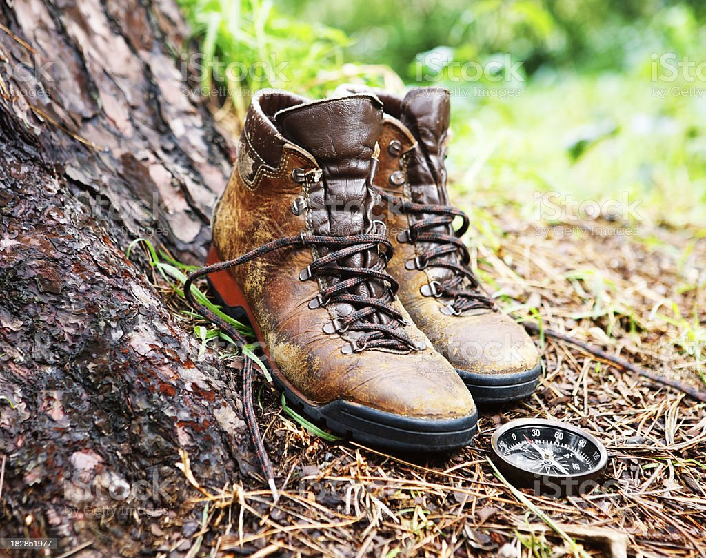 Battered old hiking boots rest against tree trunk with compass stock photo