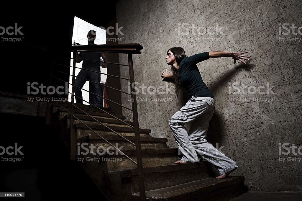 A battered woman and male silhouette on a stairwell stock photo