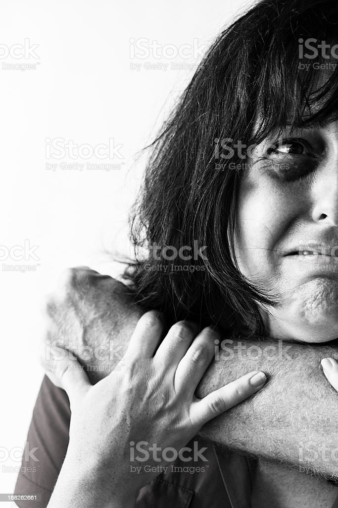 Battered woman desperately tries to escape man's encircling arm royalty-free stock photo