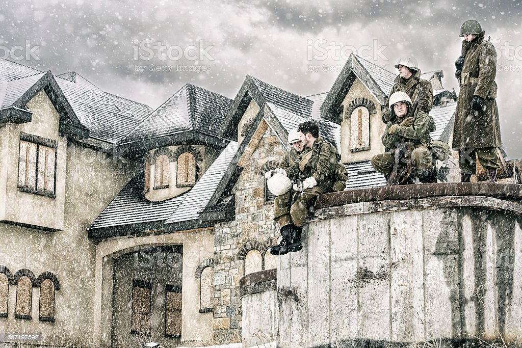 WWII Battle Weary US Soldiers Resting At Abandoned Home stock photo