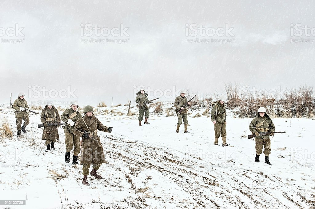 Battle Weary WWII US Squadron Walking Down A Muddy Road stock photo