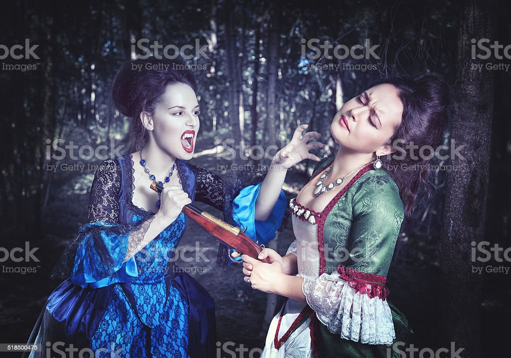 Battle with beautiful vampire in medieval dress stock photo