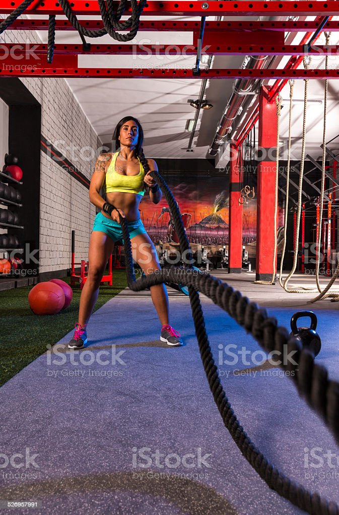 battling ropes girl at gym workout exercise stock photo