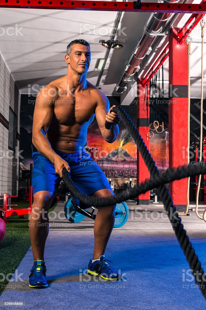 battling ropes man at gym workout exercise stock photo
