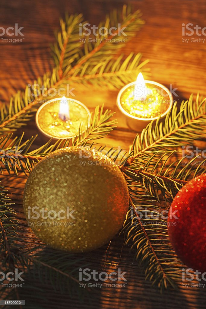 Baubles, pine branches and candles on old plank royalty-free stock photo
