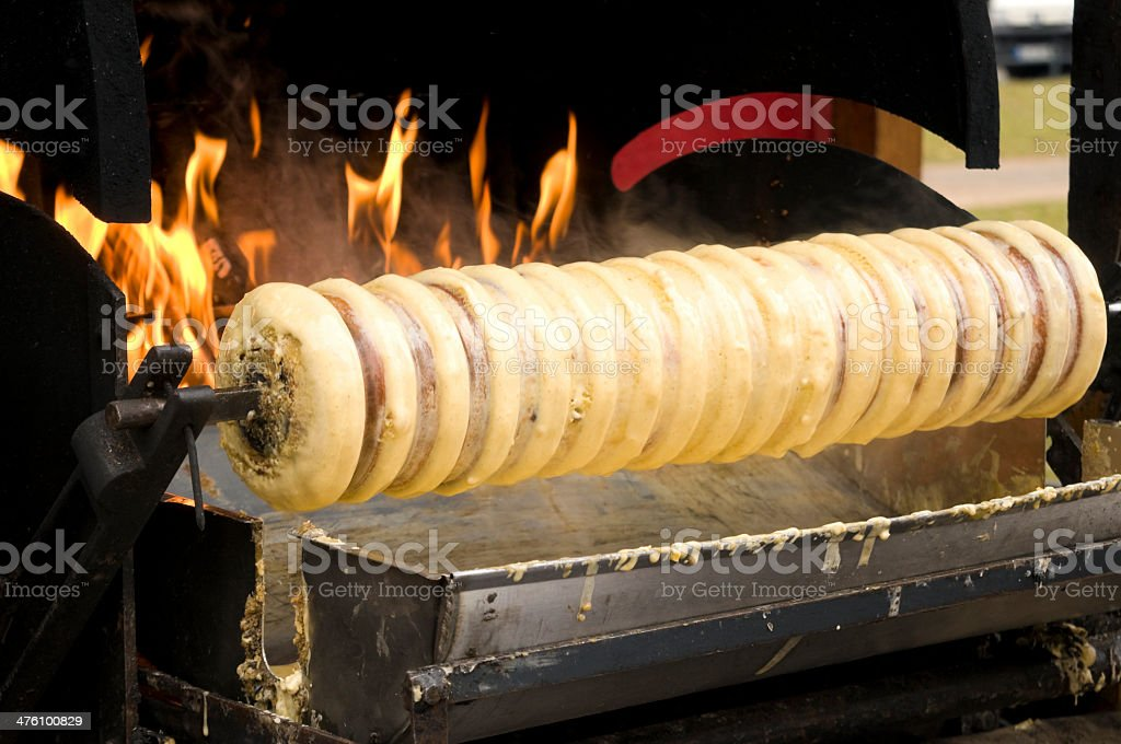 Baumkuchen, a cylindrical cake, baked over the fire stock photo