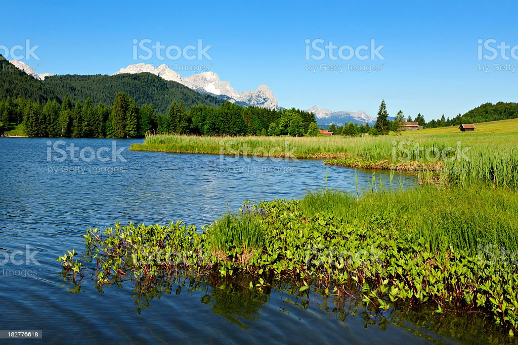 Bavaria Landscape with Lake and Barns against Mount Zugspitz royalty-free stock photo