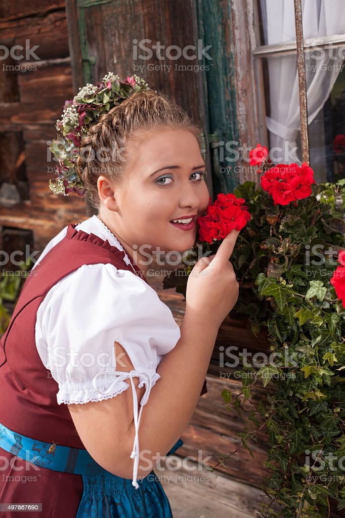 Bavarian girl in dirndl smelling a geranium. stock photo