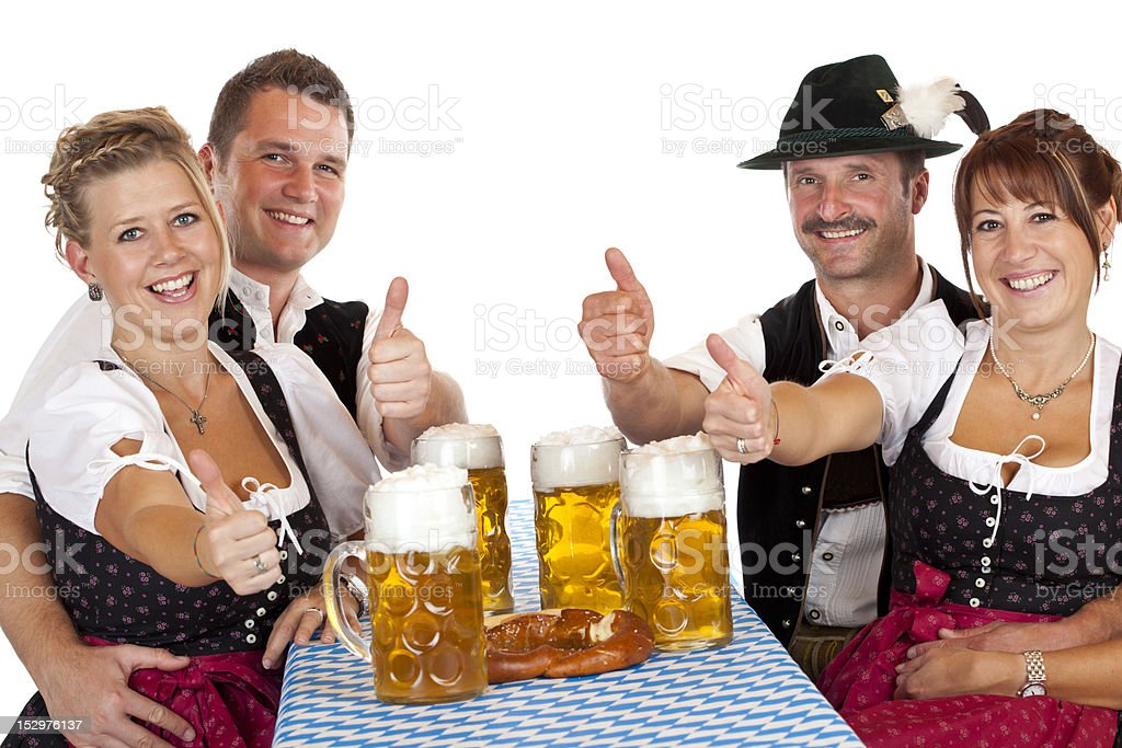 Bavarian girls and men with beer stein hold thumbs up royalty-free stock photo