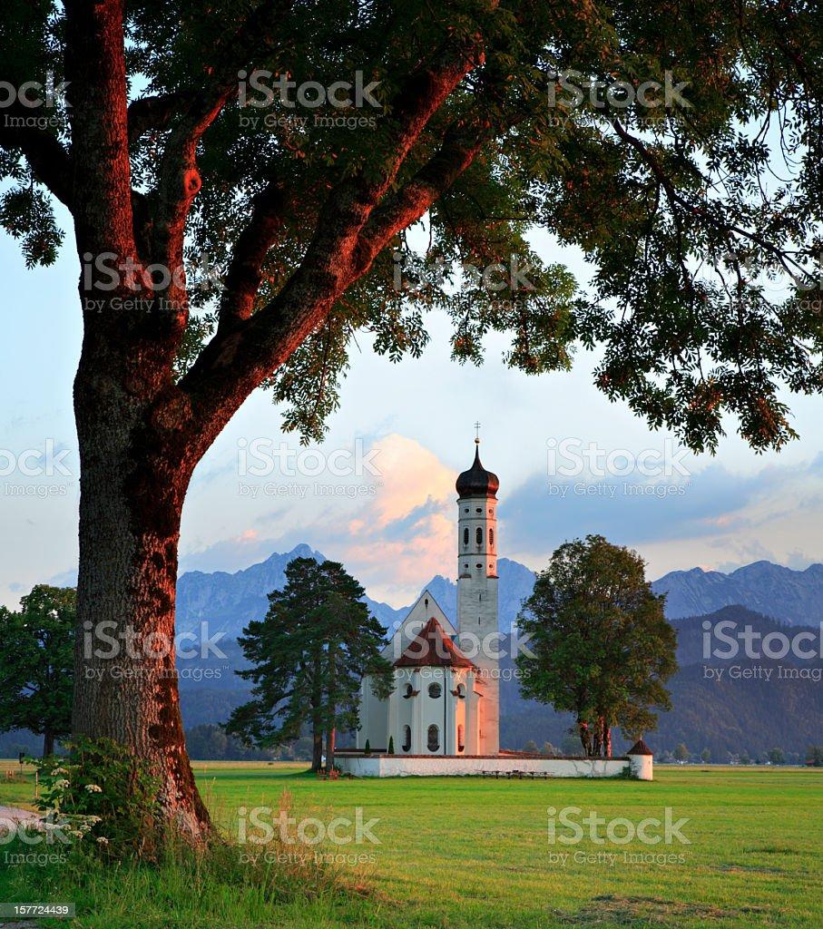 Bavarian Idyll Saint Coloman Church at Sunset against Mountain Backdrop stock photo
