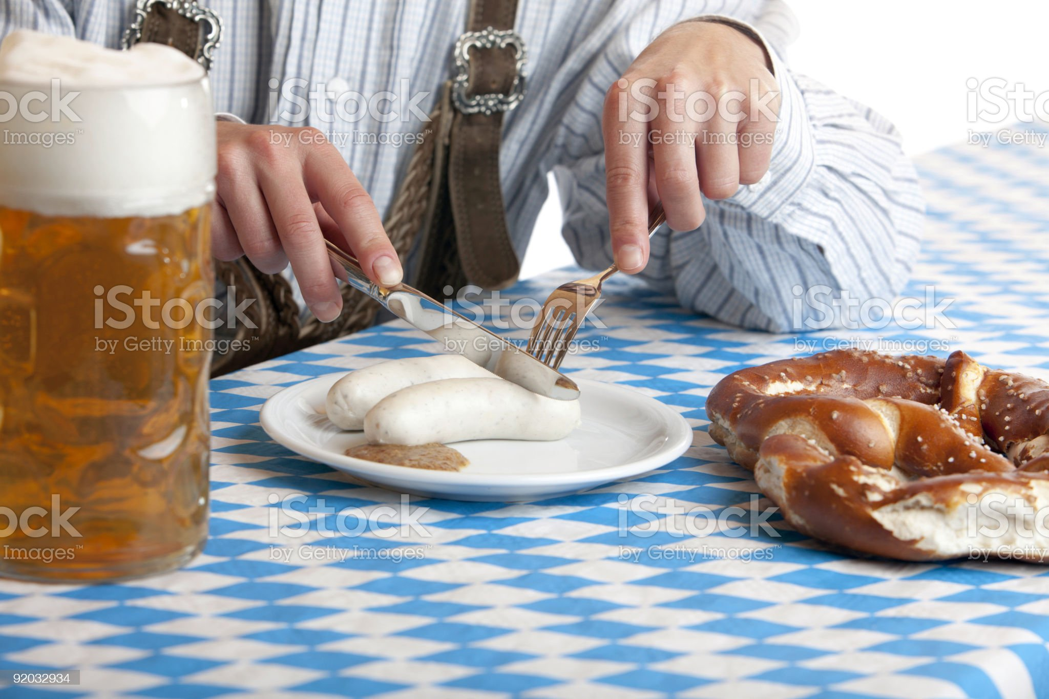 Bavarian man having lunch at Oktoberfest with 'Weisswurst' and pretzel royalty-free stock photo