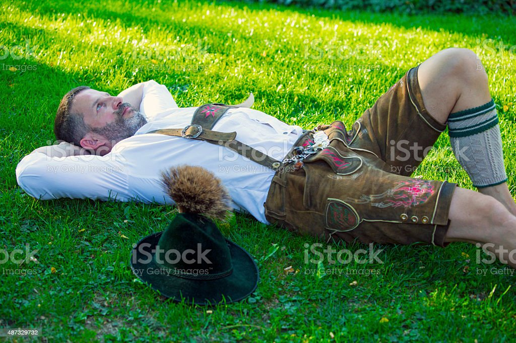 bavarian man lying on the grass stock photo