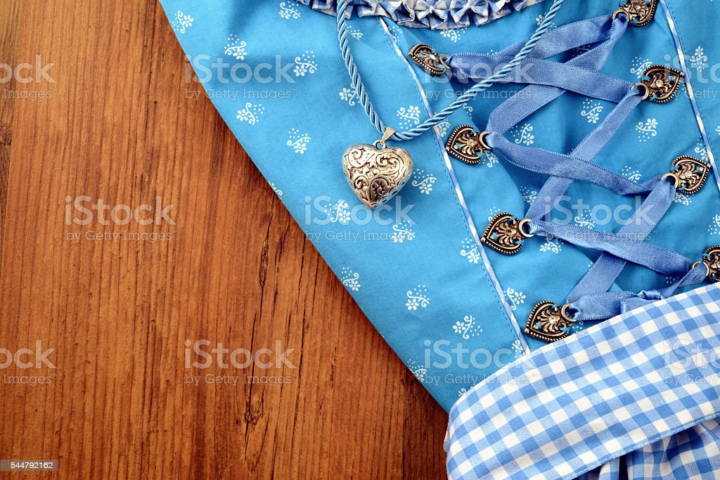 Bavarian Oktoberfest dirndle on wooden table with necklace heart stock photo