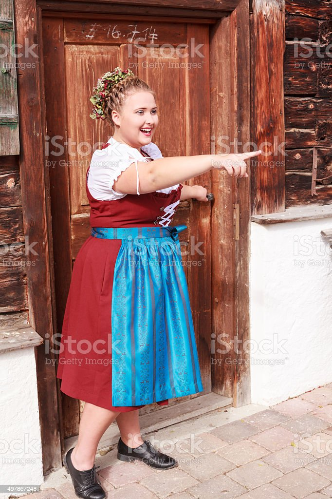 Bavarian overweight young woman in dirndl shows with finger . stock photo