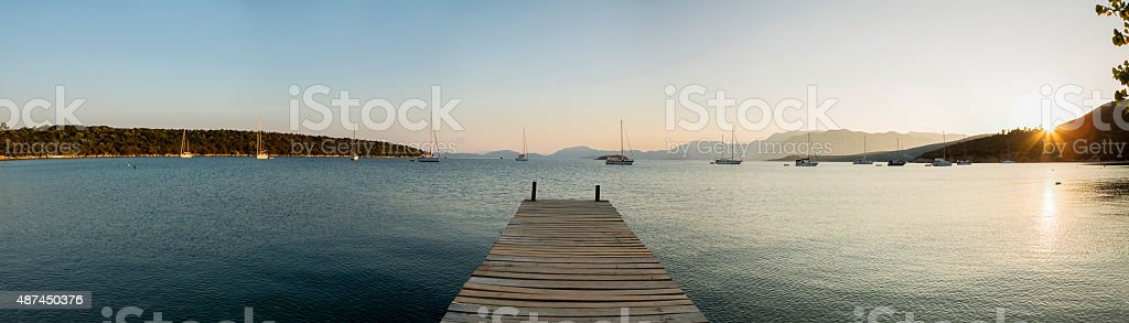 Bay at sunset with wooden pontoon and anchored sail boats stock photo