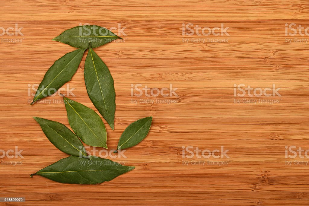 Bay laurel leaves on bamboo wooden board royalty-free stock photo