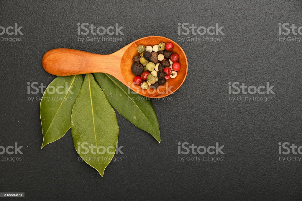 Bay leaves and pepper on black chalkboard royalty-free stock photo