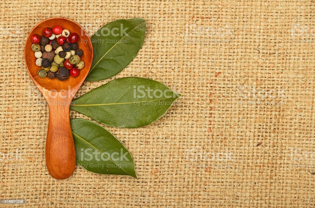 Bay leaves and peppercorn scoop on burlap canvas royalty-free stock photo