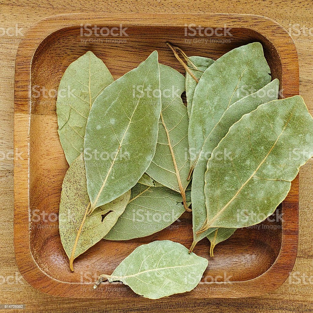 Bay leaves in a wooden tray. stock photo