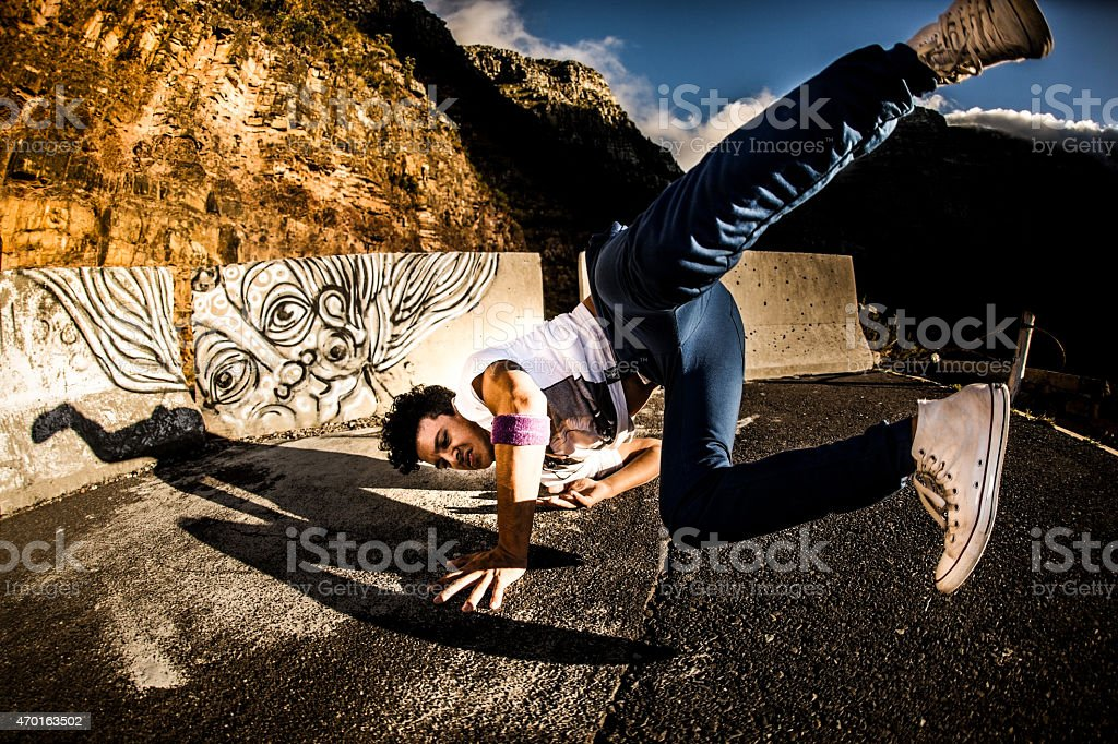 B-boy going into  shoulder spin while breakdancing on a road stock photo