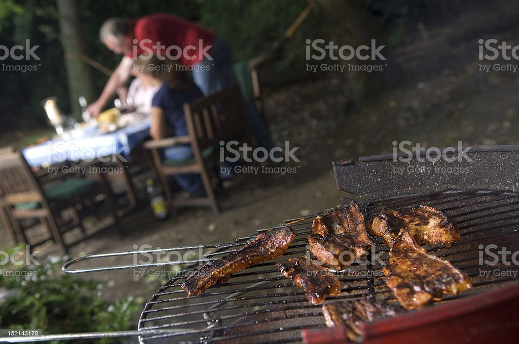 BBq with meat in foreground royalty-free stock photo