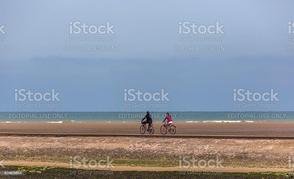 bcycling near sandy normandy coast at tide near calais france stock photo