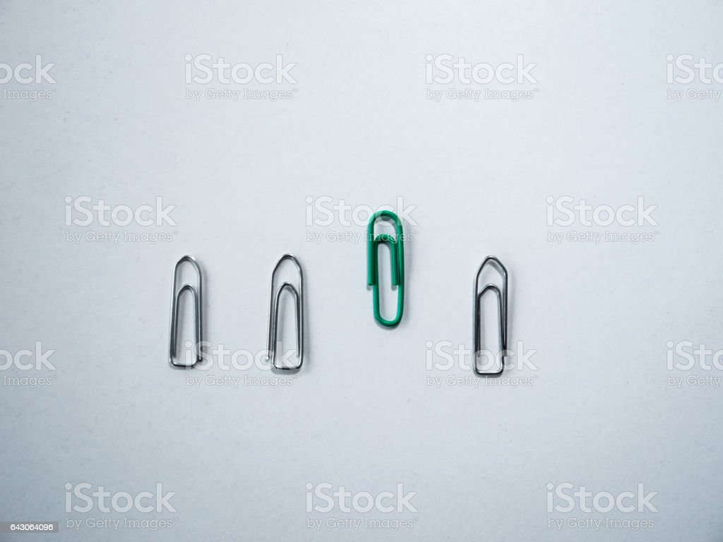 Be different: Silver and colorful paper clips on white background stock photo
