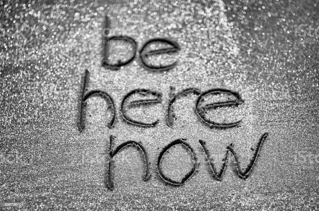 Be Here Now Handwritten in Sand stock photo