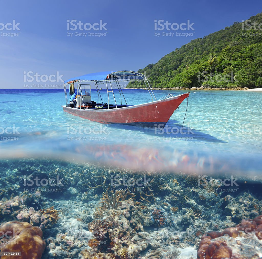 Beach and motor boat with coral reef underwater view stock photo