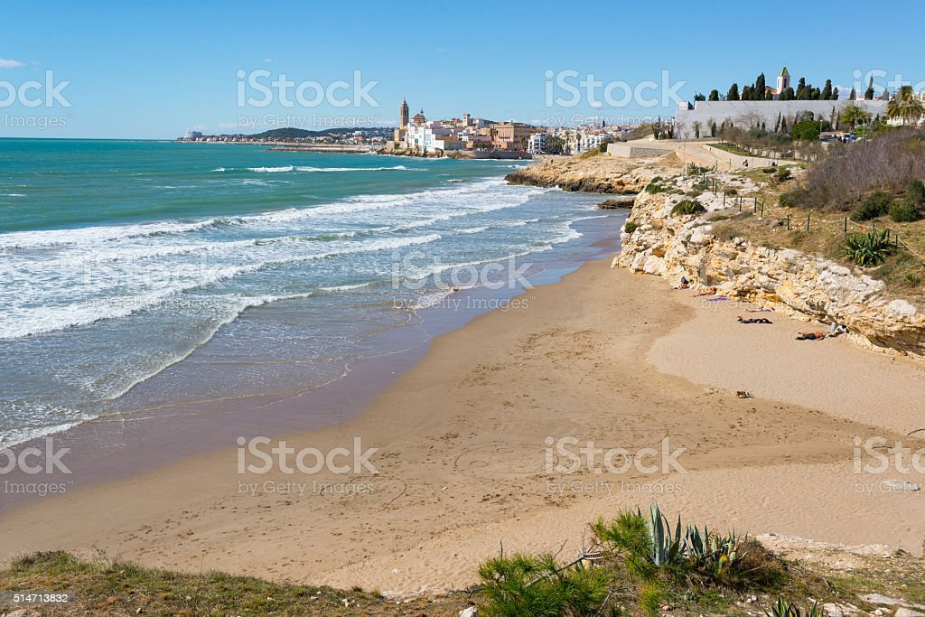Beach and rocky coast with view of town of Sitges stock photo