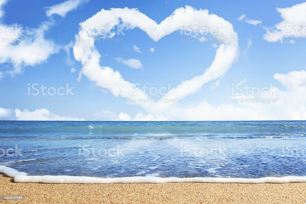 beach and sea. Heart of clouds on sky stock photo